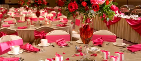 Banquet hall setup with tables and chairs in a pink and white motif