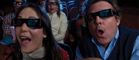 A couple wearing 3D glasses in a movie theater