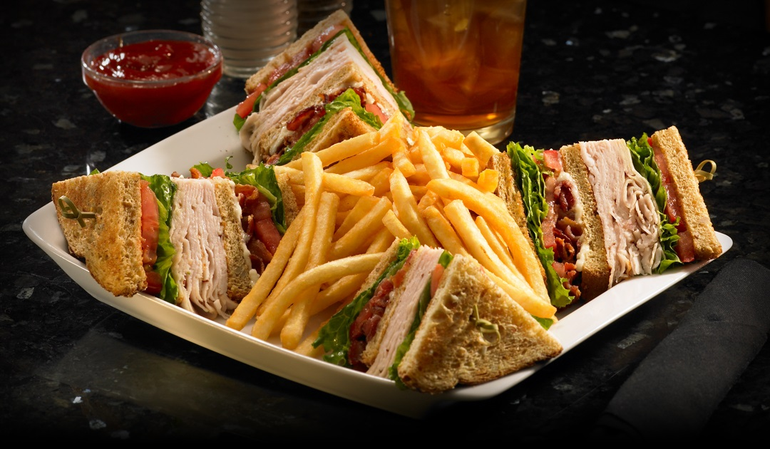 Quartered club sandwich with fries