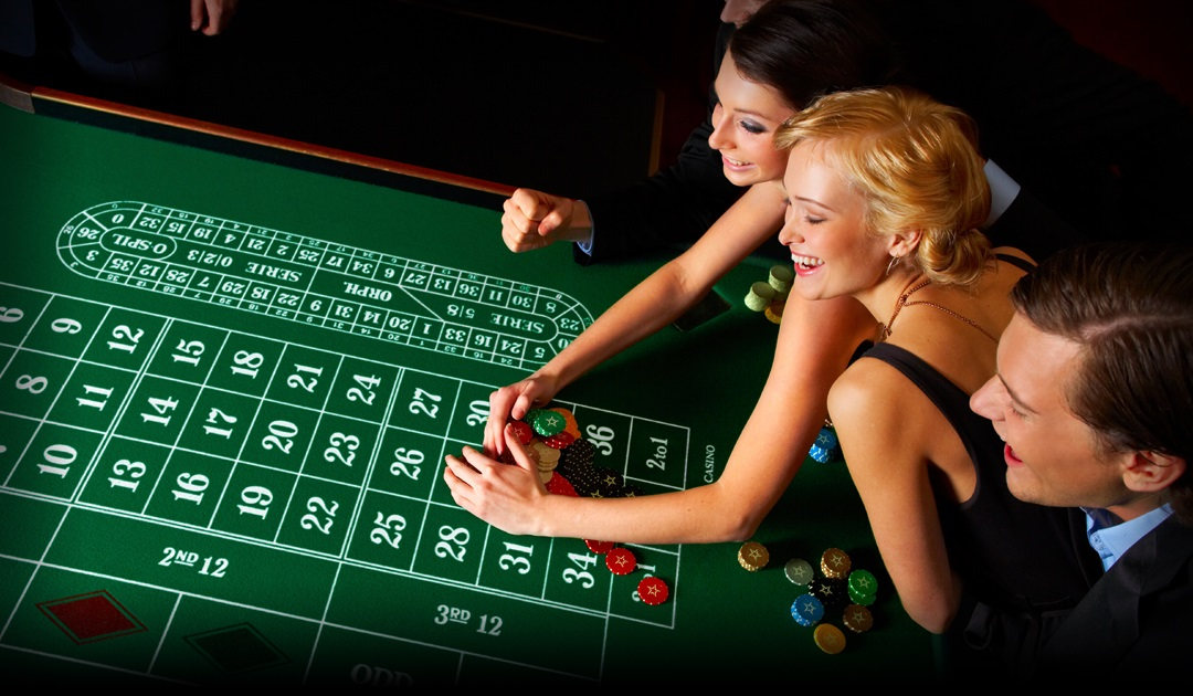 A Woman collecting winnings at the roulette table with friends observing