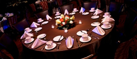 A table setup for dinner inside a ballroom or banquet hall
