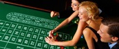 A woman collecting chips at roulette table with friends watching